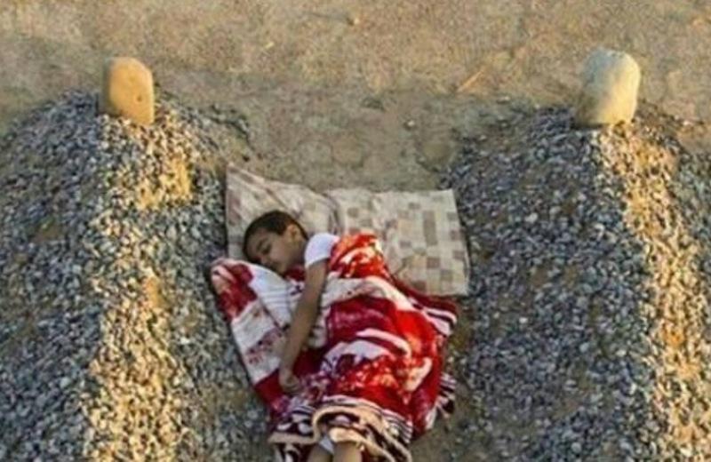 """Φωτογραφία-""""γροθιά"""" στο στομάχι: Παιδάκι κοιμάται ανάμεσα στους τάφους των γονιών του"""